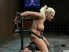 Busty blonde rides cock shaped toy in bondage scene