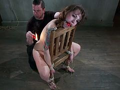 Check out what a nice tattoo and what a sexy back pretty Thorn has. Damn she's a sexy one and the way she sits on that chair fully highlights her gorgeous ass. Too bad for miss Thorn that our executor wants to play and tied her before dripping hot wax on her back. She moans with pain and that's not all!