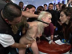 Elyssa Greene has her mouth spread open and pins on her nipples. A mistress kisses her and then, the victim is laid down on a stool and gets her pussy fingered. A large group of men and women watch as she's being tortured.