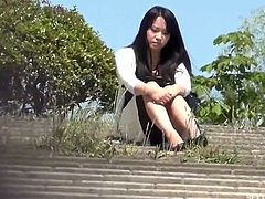 Hot asian babe is all alone on the bench at the park and shows off her big titties then spreads legs and rubs herself for a public orgasm!