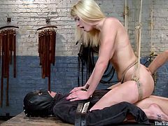 Allie is hoisted from the ceiling with rope and she kneels on the table. Below her sits a gimp who is going to have his cock use. The executor inserts the gimp's cock into the blonde slave's cunt. The ropes are used to control how she fucks him and the sex master juggles the male slave's balls.