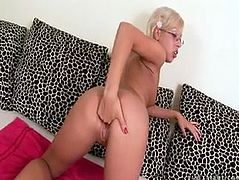 Lusty trollop Daniella is sitting naked on a couch spreading her legs wide. She inserts four fingers in her clam stretching pussy folds wide.