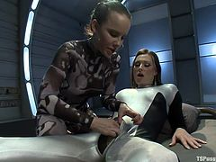 Katie St. Ives rubs and kisses Eva Cassini's thick lady-boy cock through her tight spandex. She unzips a zipper on the crotch of the suit and pulls out the shemale's cock. She then deepthroats it hard.