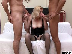 This blonde mature woman has an insatiable appetite for massive dicks in her mouth. She lays on the bed in her black lingerie and masturbates for the camera before two men with hard cocks enter the picture. She sucks on them both moving her head side to side.