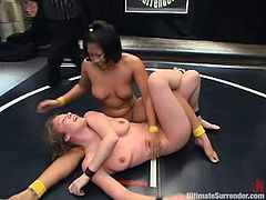 Watch this busty blonde being fucked by this Asian hottie with a large strapon after loosing the match to her.