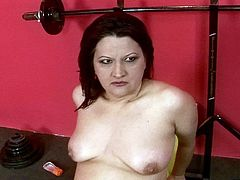 Flamboyant whorish brunette mom lies on the fitness machine while tickling her bushy pussy with all kinds of sex toys before a kinky dude joins her to pound it with a dildo.
