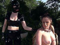 Nasty Latex Lucy with huge tits and big ass in kinky outfit and stripper shoes uses strap on to fuck naked brunette cutie Samantha Bentley in the ass in memorable bondage fantasy.