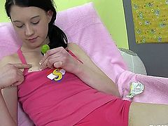 Sweet brunette teen nymphet with small tits rubbing her petite pussy with a green lollipop