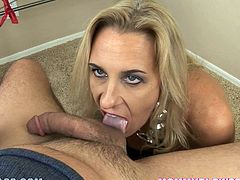 Slutty mature blonde Amber Lynn is getting naughty with some dude indoors. She licks his prick and balls and also rubs his dick against her big natural tits,
