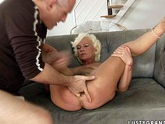 This lascivious granny will never miss a chance for a good, hard fuck. She spreads her legs wide to let her lover finger her asshole. Then he licks her hairy snatch.