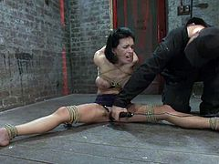 Kinky brunette chick sits on the floor with her legs wide opened. She gets her tits tortured with ropes and pussy toyed with a vibrator.