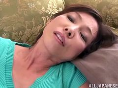 Japanese lady takes her skirt off and lies down on a sofa. Then she starts to finger her hairy pussy skillfully.