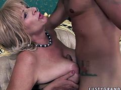 Bosomy blond mature BBW uses her oversized jugs to give a titfuck to horny young dude before she lies on her back to welcome a poke of her hairy pussy in missionary style.
