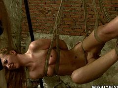 Wanton long haired amateur gets hanged to the ceiling by insatiable domina who arouses her naked body with a metal spiked roller and later slaps in peppering BDSM sex video by 21 Sextury.