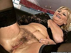 This immense blond BBW is a real nympho. She lies on the leather couch with legs wide open allowing a rapacious grey-haired dad dildo fuck her bearded vagina and later finger it.