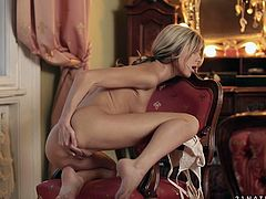 Divine blond amateur sits on the luxurious chair while her hands are busy stroking both her small perky tits and bald unused v
