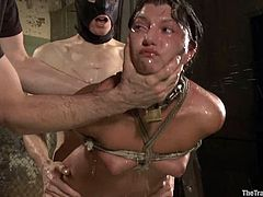Tied up brunette babe gets her shaved pussy toyed. After that she gives a blowjob and gets fucked from behind by a guy in mask.