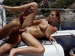 Slutty redhead girl takes her bikini off and gets her tits fondled. Later on she lies down on a deck and gets fucked deep in her shaved pussy.