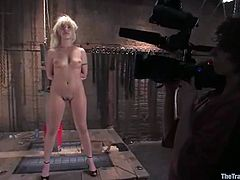 Satine Phoenix is getting naughty with Maestro in a basement. She lets the man immobilize her in a pillory and then enjoys his hard cock in her tight pussy.
