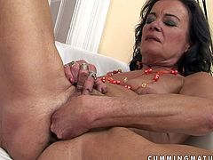 Naughty granny with hairy pussy is lying naked on a couch. She stretches her vaginal folds exposing her depth. She fingers her clam actively. Then she stuffs her cunt with big fat dildo moving it in and out intensively.