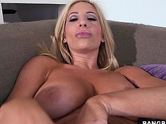Amazingly hot blonde chick with big boobs strips her clothes off and lies down on a sofa. She spreads her legs and fingers the pussy with two hands.