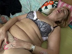 Granny Emmy keeps a hot bush between her thighs. Her tight, unshaved vagina needs a serious fuck so she grabs her red dildo after pinching her nipples and slides it between her pussy lips. The old whore moans as she fucks herself and desires a real cock to be shoved deep in her vagina.