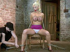 She is tied up and her legs are spread on the spreader bar. Her master sticks some tools in her pussy and she just can't go loud, as she is ball gagged.