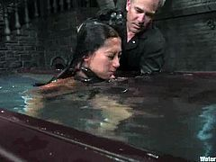 Slim and hot brunette girl lies on the floor being tied up. She gets her ass whipped and then her master waters her with powerful jet of water.