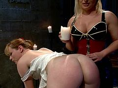 Claire Robbins and lewd blonde dominatrix Katja Kassin are having fun in a basement. Katja pours wax onto Claire's ass and then hurts the bitch and fucks her juicy cunt with a toy.
