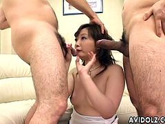 Cute and charming Asian pornstar Junna Aikawa on her knees taking two mushroom heads in her mouth and wanking it 