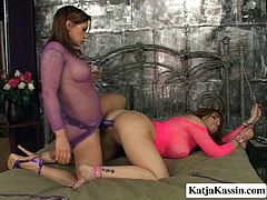 Hot blooded fuckable red-haired mature stands in doggy pose wearing fishnet tank while a young pitiless domina pokes her vagina with a strap on before they switch to sideways position.