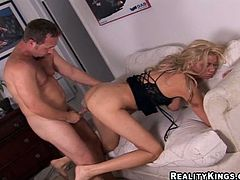 Hot blonde MILF in a corset gets her juicy boobs licked and pussy fondled. After that she lies down on a bed and gets her pink pussy destroyed.