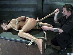 Amazing brunette babe lies being tied up with ropes. She gets her ass and pussy toyed at the same time. Then she also rides a dildo.