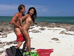 Engaging Asian chick is playing dirty games with some guy on a beach. They kiss and caress each other and then fuck in the reverse cowgirl and other positions on the sand.