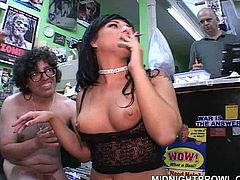 Wanton brunette hottie in black lingerie and fishnet stockings stands on her knees surrounded by a crowd of horny dudes whom she gives blowjob in turns in gangbang sex video by Pornstar.
