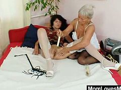 Brunette and blonde mature women take their lingerie off and play with each others hairy pussies in a bedroom.