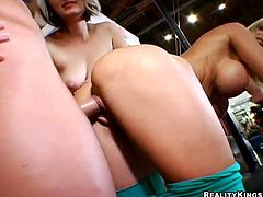 Blonde girls in sportswear have an amazing sex with muscular guy in the gym. They give him a blowjob and a handjob. After that they get rammed from behind.