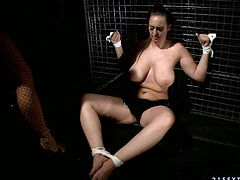 Slutty bitch with big boobs is tied up in the basement. Tough mistress thrusts huge black dildo into her mouth pushing the tool deep in her throat. She makes her sex slave suck the toy furiously. Submissive girl follows all instructions of her mistress.