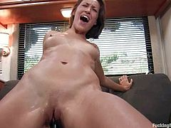 Sexy brown-haired babe stands on all fours getting her vagina drilled deep and hard from behind by the fucking machine.