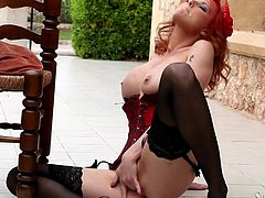 Stunning redhead girl in a corset and stockings makes hot solo show in a backyard. She sits down on the floor and fondles her smooth pussy.