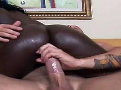 Busty black bitch Shanti is having fun with a white guy indoors. She oils her jugs and lets the man squeeze them and then they have hot sex in the reverse cowgirl position.