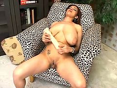 Hot chick with big hanging boobs lies on an armchair with her legs wide opened. She takes realistic dildo and toys her pussy. Then she licks the dildo to taste her juices.