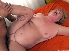 Chubby mature hoochie gets her old pussy drilled hard by one young guy. He pokes her in missionary style and her fat rolls bounce.