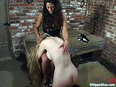 Slim blonde girl fingers herself and gets spanked in a dungeon by brunette mistress. Later on she gets her chained and toyed with big dildo.