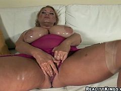 Blonde woman with oils up her gigantic boobs. Then she gives hot blowjob and gets fucked rough on a sofa.