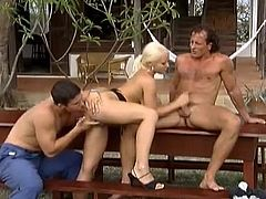 Sexy blonde girl with nice boobs takes her clothes off and lies down on a table. She gives a blowjob and gets fucked at the same time. Then two guys cum on her breast.
