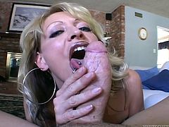 A lewd mature blonde kneels in front of some guy and begins to stroke his schlong with her pierced tongue. The she takes the fat sausage into her pussy and gets it fucked hard doggy style.