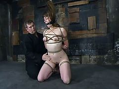 Slim brown-haired babe gets undressed and tied up. Later on a guy fixes claws to her nipples and stuffs the pussy with a dildo.