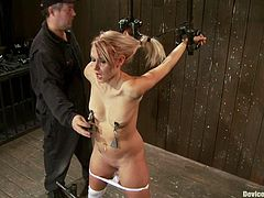 Hot blonde gets bounded. Then her master fixes claws with weights to her nipples. Later on she also gets her vagina toyed with black vibrator.