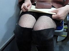 Touching her legs in fishnet stockings in a bus